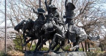 a huge Remington replica has cowboys and horses galloping through the gardens