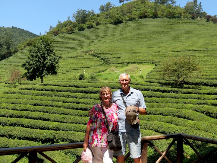 the author and her husband, Rod Mackie, with a backdrop of tea bushes (each of those rows is made up of hundreds of tea bushes)
