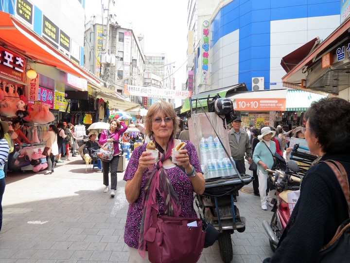 Vmarket: the author holding two ho-duks, a kind of sweet rice-flour pancake in Namdaemun Market