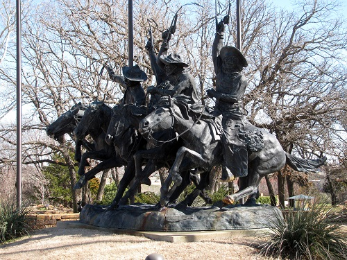 a huge Remington replica has cowboys and horses galloping through the gardens