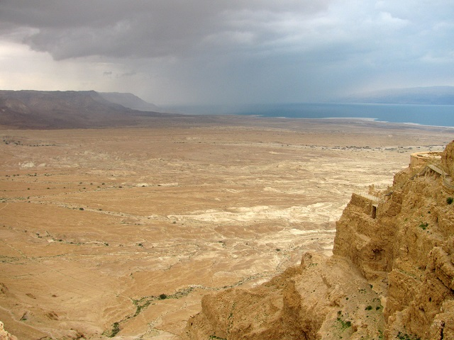 from this vantage point you can clearly see the three levels of Herod's Palace, with looming storm clouds over the desert