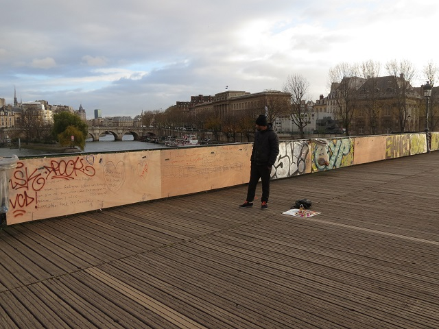 a hopeful lock vendor stands on the boarded-up bridge